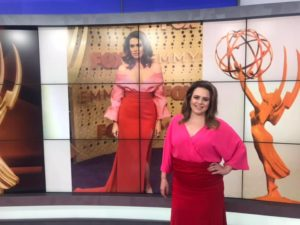 Emily modeling Mandy Moore's playful red and pink dress and voluminous curls